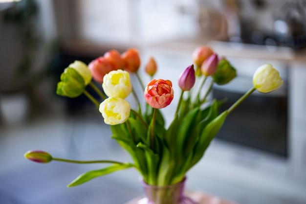 Glazen vaas met boeket van prachtige tulpen op bakstenen muur muur