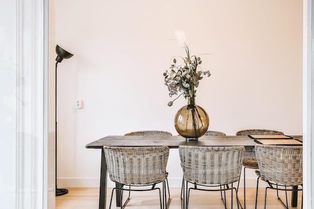 Glazen vaas met bos verse bloemen op tafel met stoelen in een stijlvolle eetkamer thuis at