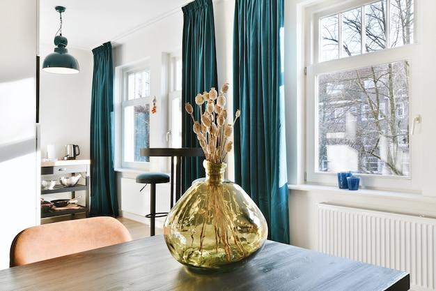 Glazen vaas met decoratieve gedroogde planten geplaatst op houten eettafel in modern appartement