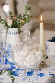 Glazen vaas met dessert marshmallow staat op de tafel, bedekt met een tafelkleed met een patroon gzhel. naast de kaars brandt. decor met een feestelijk diner of lunch