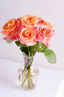 Glazen vaas met mooi boeket van verse natuurlijke rozen bloemen op een tafel bedekt wit doek tegen licht grijze muur.