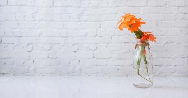 Glazen vaas met oranje mooie bloem op witte tafel.