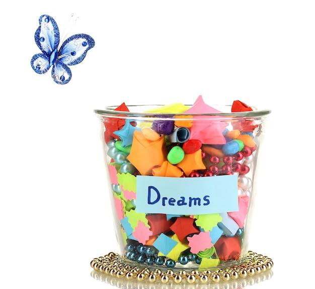 Glazen vaas met papieren sterren met dromen op wit wordt geïsoleerd