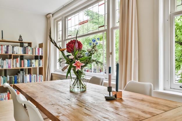 Glazen vaas met verse bloemen en stijlvolle kaarsen op houten tafel tegen ramen en boekenkast in lichte eetkamer