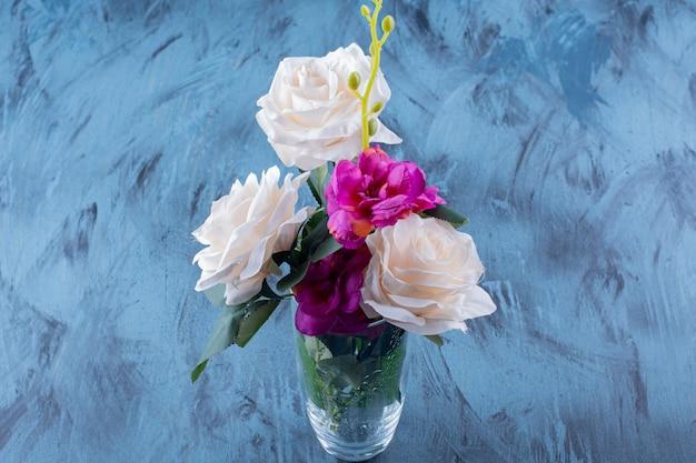 Glazen vaas met witte roos en paarse bloemen op blauw.
