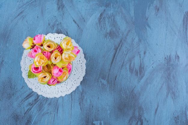 Glazen vaas van kleurrijk bloemstuk op blauw.