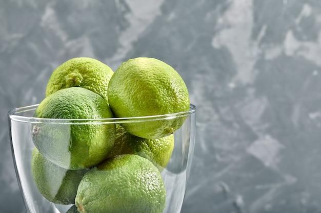 Glazen vaas vol groene limoenen op concrete achtergrond.