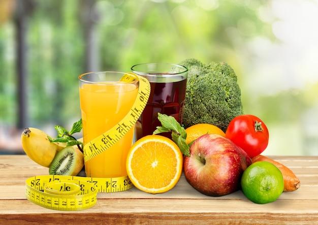 Glazen vers sap en fruit met groenten en meetlint
