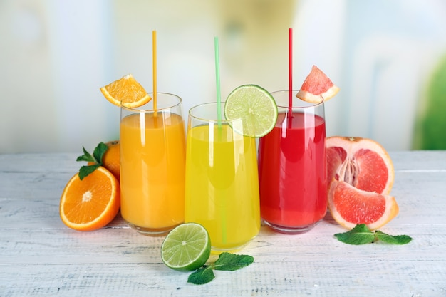 Glazen verschillende sap met fruit en munt op witte houten tafel