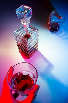 Glazen vierkante karaf met sterke drank met twee glazen glazen. twee mensen drinken alcohol uitzicht van bovenaf