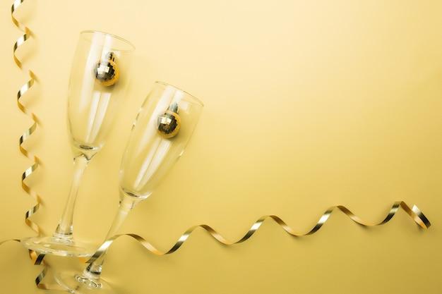 Glazen voor mousserende wijn, kerstboomballen en lint.