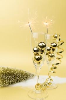 Glazen voor mousserende wijn, sterretjes, kerstboomballen en gouden lint