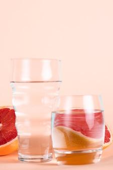 Glazen water met half rode sinaasappels