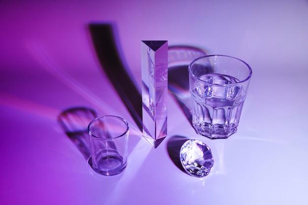 Glazen water; prisma; diamant met schaduw op paarse achtergrond