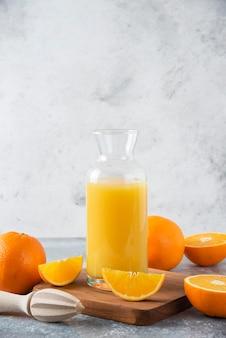Glazen werper sap met vers oranje fruit op een houten bord.