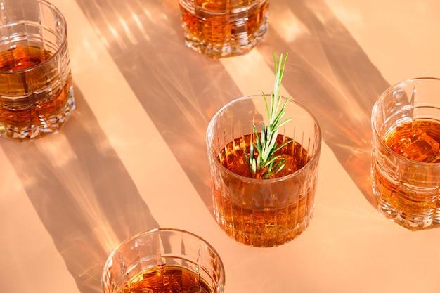 Glazen whisky met ijsblokje op beige.
