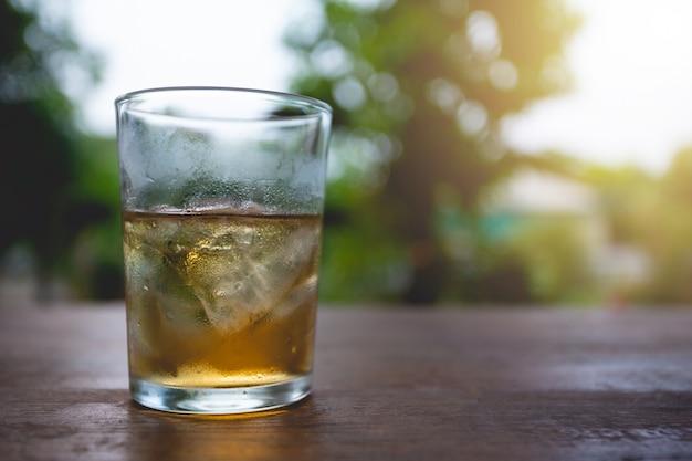 Glazen whisky met ijsblokjes op hout.