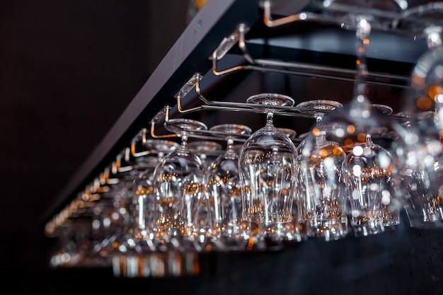 Glazen wijn. glazen hangen boven de bar in het restaurant. lege glazen voor wijn. wijn en martini-glazen in plank boven een barrek in restaurant