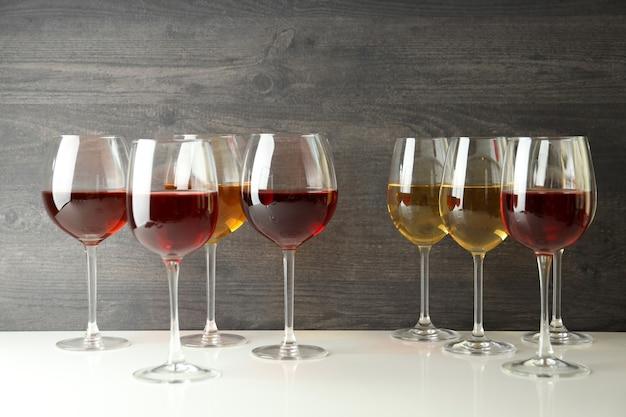 Glazen wijn op witte tafel tegen houten achtergrond