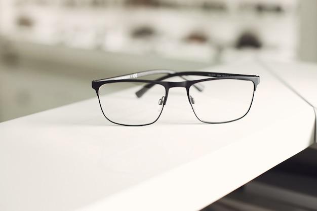 Glazen witte achtergrond. recht in zicht. reclamefoto van afgeronde metalen brillen. mode optische concept