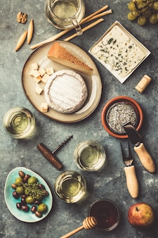 Glazen witte schuimwijn met kaas, druiven, noten, oliv