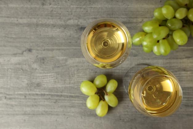 Glazen witte wijn en druif op grijze getextureerde tafel