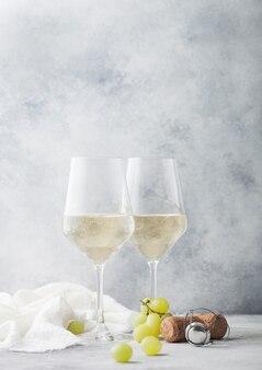 Glazen witte zelfgemaakte zomer verfrissende wijn met kurken en druiven op lichte stenen achtergrond.