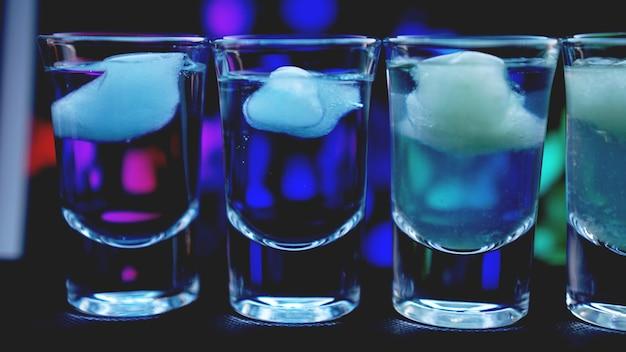 Glazen wodka met ijs. in bar - neonachtergrond