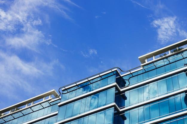 Glazen wolkenkrabber gebouw met bewolkte blauwe hemelachtergrond