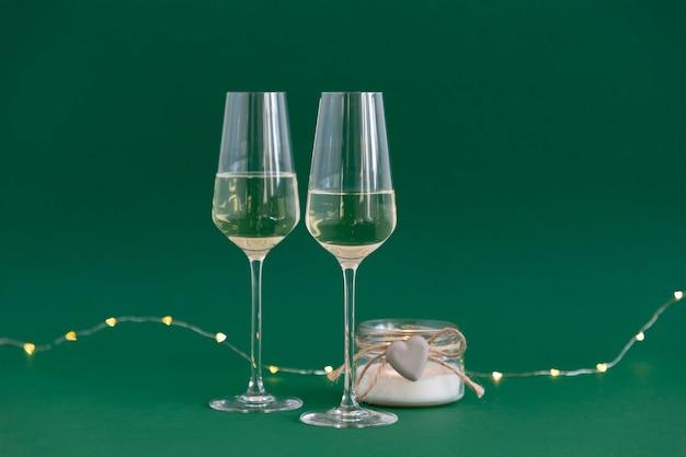 Glazen zijn gevuld met champagne en kaars tegen de groene achtergrond van harten bokeh lichten.