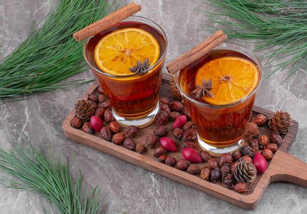 Glazen zwarte thee met plakjes citroen op houten snijplank.