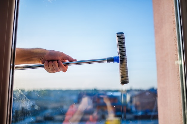 Glazenwassen in hoogbouw, huizen met een borstel. reinigingsborstel voor ramen. groot raam in een gebouw met meerdere verdiepingen, schoonmaakservice. stof verwijderen en glas wassen.