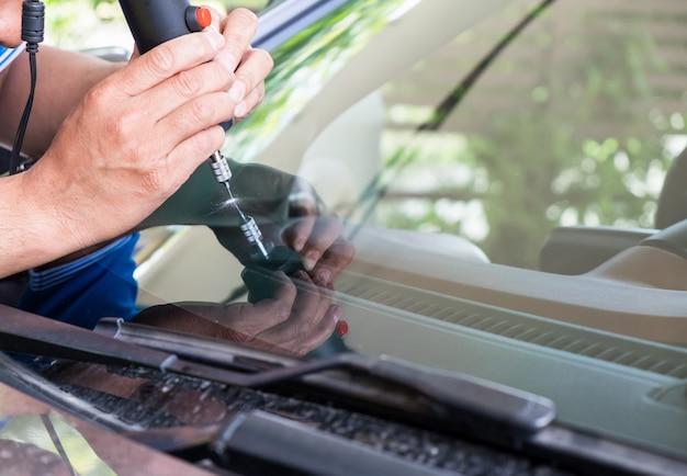 Glazier met behulp van gereedschappen die repareren om scheuren op te lossen