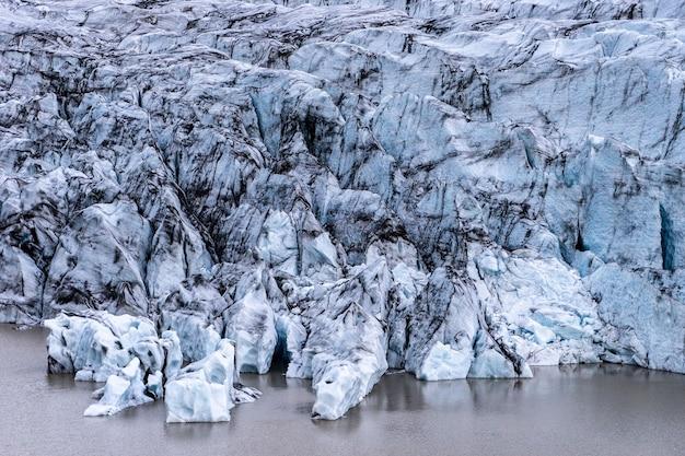 Gletsjerdetails met as in het ijs