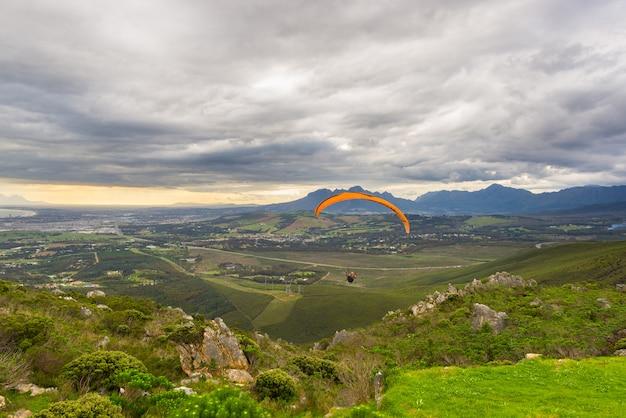 Glijscherm dat over de groene bergen vliegt