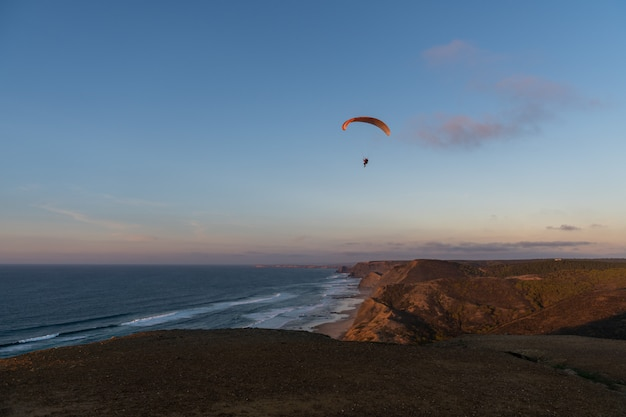 Glijscherm dat over de kust bij zonsondergang vliegt. paragliding sport