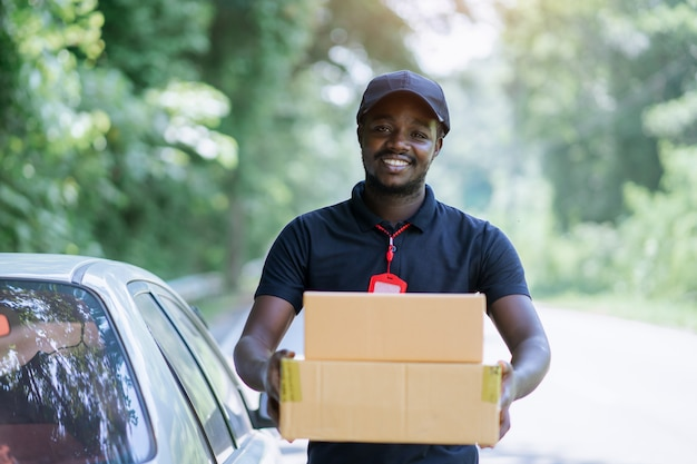 Glimlach afrikaanse mannelijke postbezorging koerier man voor auto leveren pakket