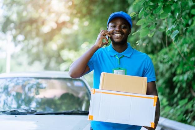 Glimlach afrikaanse post koerier man voor auto leveren pakket met sprekende smartphone.