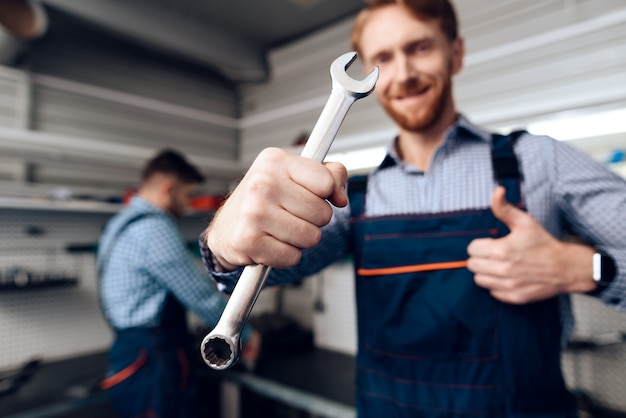 Glimlach automonteur poseren met sleutel.