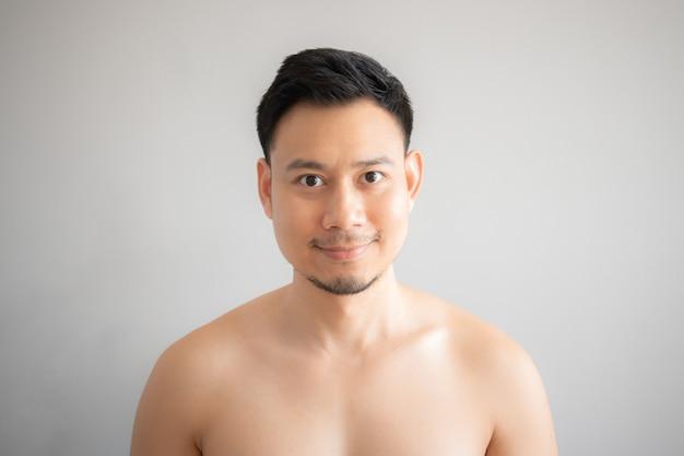 Glimlach aziatische die mens in topless portret op grijze achtergrond wordt geïsoleerd