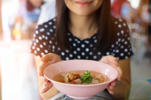 Glimlach aziatische vrouw die een kom noedel in restaurant houden