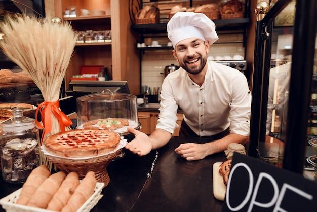 Glimlach bebaarde man in schort permanent in bakkerij.