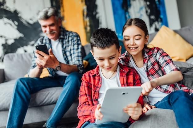 Glimlach broer en zus spelen spel op laptop met hun grootvader.