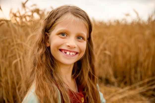 Glimlach dag. het meisje glimlacht. mooi meisje lacht. de glimlach van kinderen. gelukkig meisje. het kind lacht.