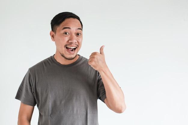 Glimlach en blije gezichtsuitdrukking van aziatische man wijzen op een lege ruimte met inhoud reclamemodelconcept