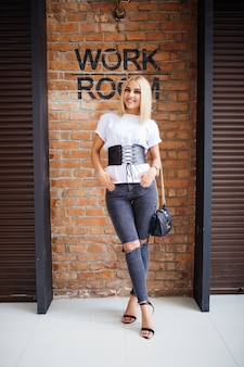Glimlach gelukkig blond meisje dichtbij oude bakstenen muur