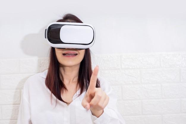 Glimlach gelukkige vrouw die ervaring opdoet met het gebruik van vr-headset-brillen van virtual reality thuis