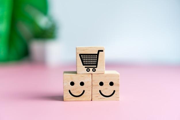 Glimlach gezicht en kar pictogram op houten kubus. optimistisch persoon of mensen gevoel van binnen en service rating bij het winkelen, tevredenheid concept.