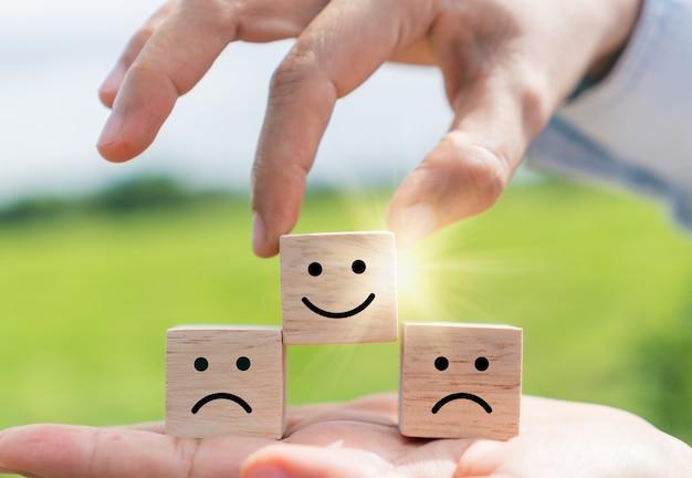 Glimlach gezicht en kar pictogram op houten kubus. optimistische persoon of mensen die zich binnen voelen en servicebeoordeling bij het winkelen, tevredenheidsconcept in het bedrijfsleven.