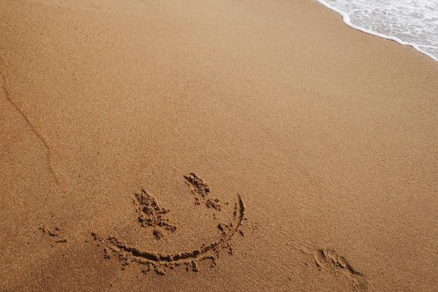Glimlach gezicht op zand